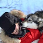 Huskey freut sich und leckt seinen Besitzer ab