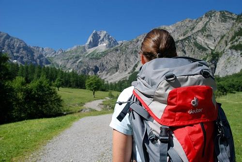 Frau mit Rucksack vor Bergpanorama