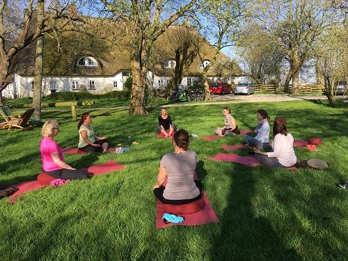 Yoga im Freien vor einem Reethaus
