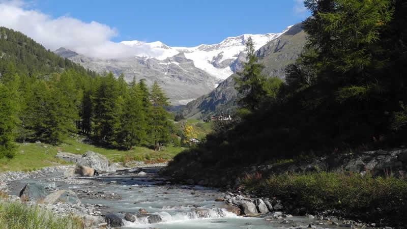 Bergpanorama mit schneebedecktem Monte Rosa und Gebirgsfluss