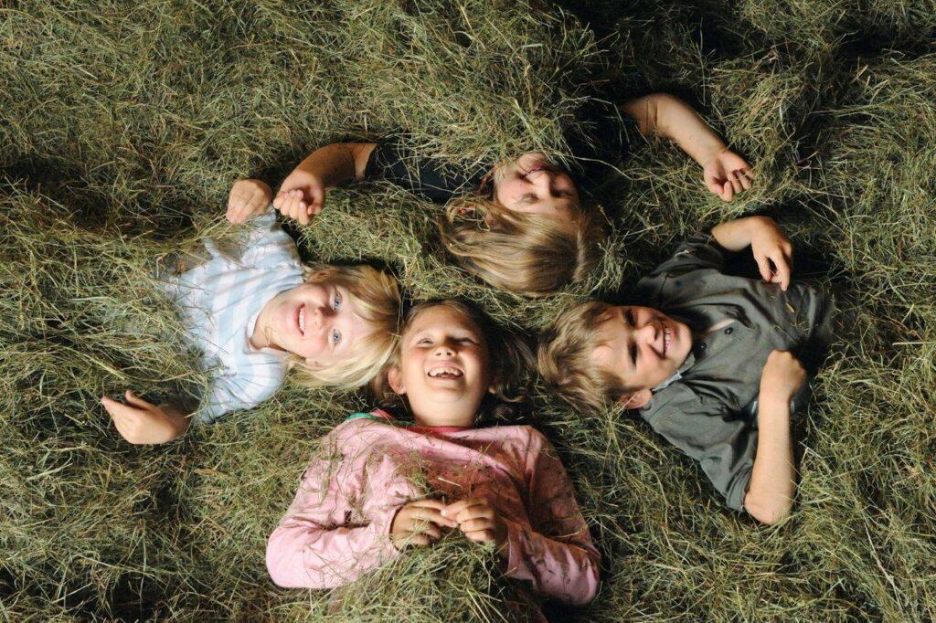 Vier Kinder liegen im Heubett